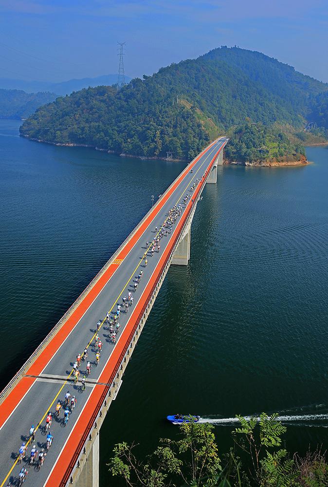 杭州第八届千岛湖国际公路自行车赛的车队驶过千岛湖上的小金山大桥 .